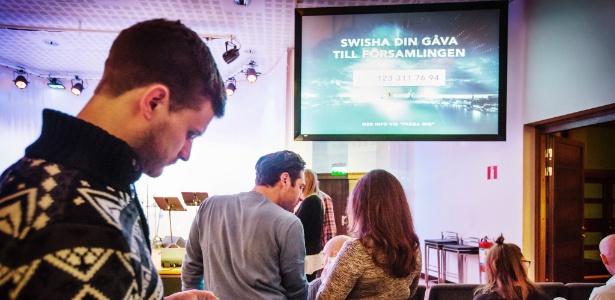 Em igreja de Estocolmo, fiéis pagam dízimo pelo celular. A Suécia avança para um futuro sem dinheiro vivo