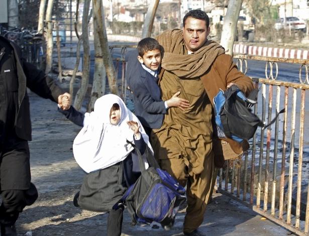 13.jan.2016 - Homem carrega filho após explosão próximo ao consulado paquistanês em Jalalabad, no Afeganistão. Pelo menos sete integrantes das forças afegãs morreram em um ataque com bombas e tiros perto do consulado