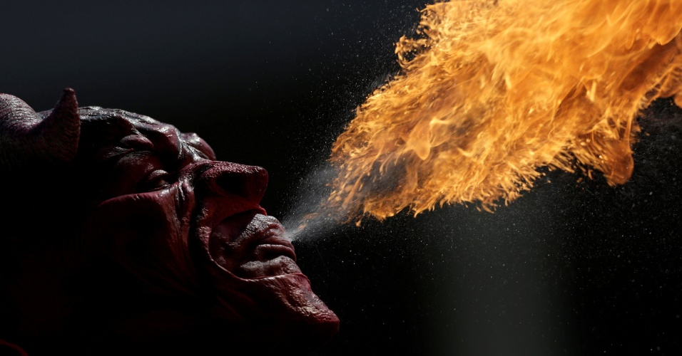 1.nov.2016 - Homem usando uma máscara do diabo, faz performance na rua cuspindo fogo em Monterrey, no México