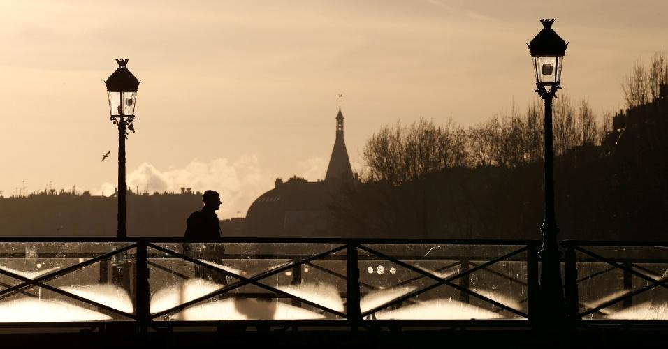 28.dez.2016 - Homem anda em ponte sobre o rio Sena durante o pôr do sol em Paris, França