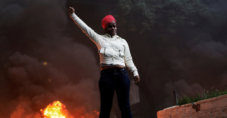 28.abr.2017 - Manifestante faz gesto de resistência em frente a uma barricada com fogo em São Paulo. Na zona central da cidade, o protesto teve confronto entre a polícia, que chegou a usar bombas de gás, e os manifestantes