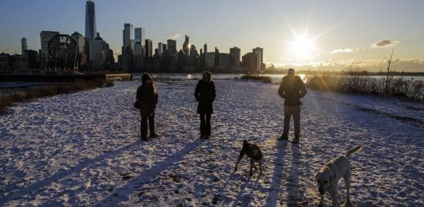 Pessoas caminham com cachorros de estimação em dia de céu ensolarado e temperaturas congelantes em Nova York
