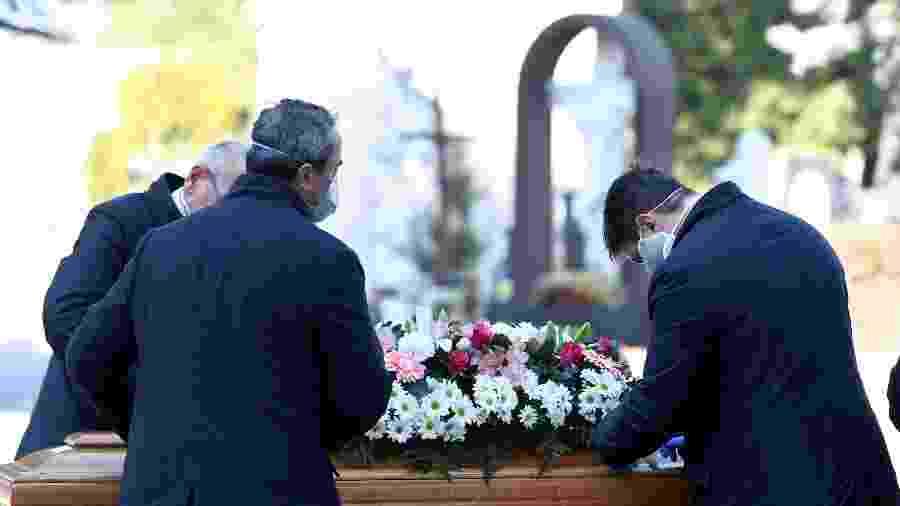 Agentes funerários e funcionários de cemitério trabalham com máscaras protetivas ao transportar caixão de vítima da covid-19 - Flavio Lo Scalzo/Reuters