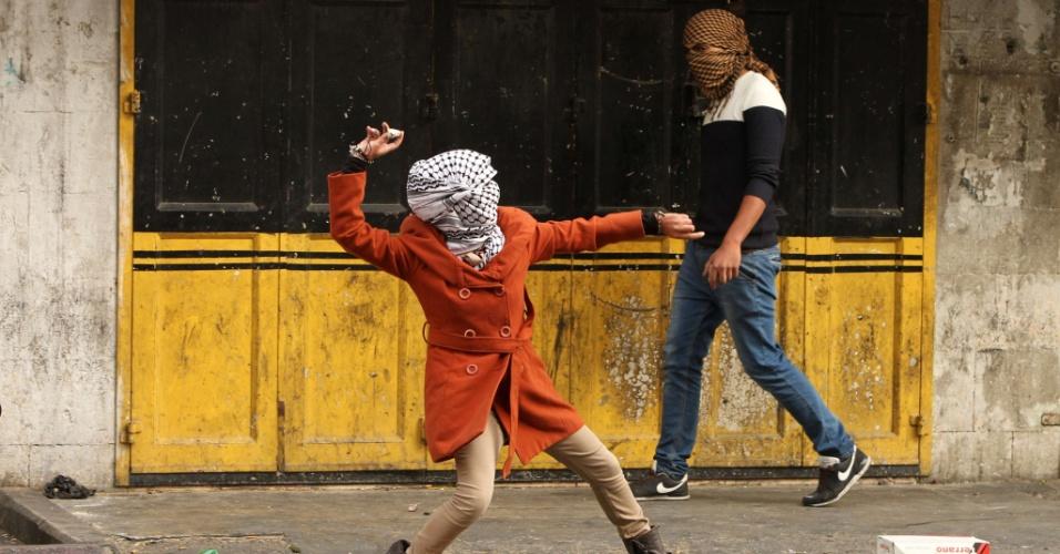 5.nov.2015 - Palestina lança pedra contra forças de segurança israelenses durante confrontos no centro da cidade de Hebron, na Cisjordânia. A violência entre palestinos e israelenses crescente na região já deixou dezenas de mortos entre ambos os povos