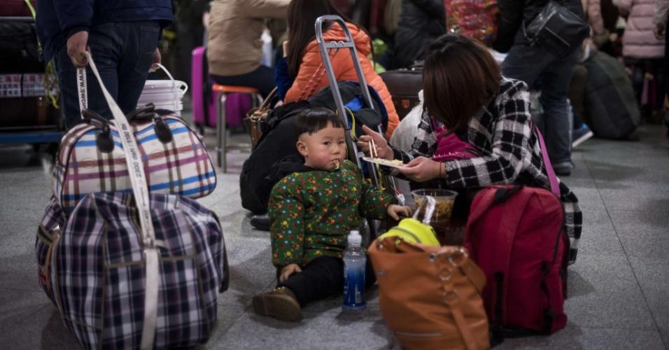 29.jan.2016 - Mãe alimente criança enquanto aguarda para embarcar em estação de trem em Xangai. O movimento estimado para o Ano-Novo chinês é de 2,9 bilhões de viagens no país.