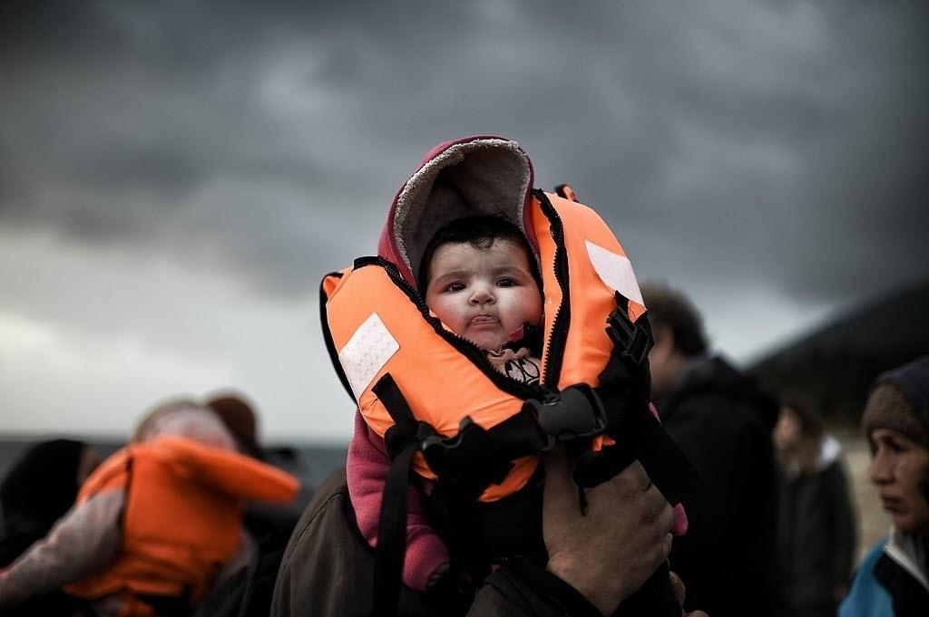 19.fev.2016 - Um refugiado segura seu filho ainda de colete salva-vidas ao conseguir chegar na ilha de Lesbos, na Grécia. O barco em que estavam partiu da Turquia e atravessou o mar Egeu