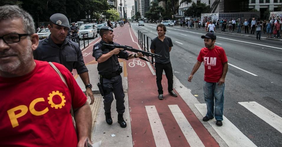 18.mar.2016 - Policial aponta arma para manifestante na avenida Paulista, em São Paulo, após briga entre os que protestavam contra e a favor do impeachment da presidente Dilma em frente ao Masp