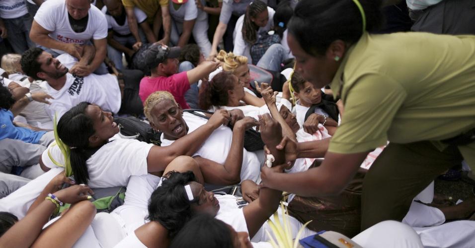 20.mar.2016 - Policiais femininas prendem uma das integrantes das Damas de Branco, grupo dissidente que luta pela libertação de presos políticos em Cuba, durante protesto em Havana horas antes da chegada de Obama