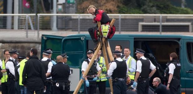 Equipe de segurança cerca manifestantes do movimento Black Lives Matter depois que eles se acorrentaram na pista do London City, no Reino Unido