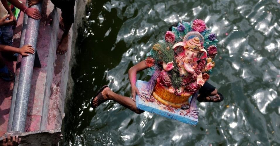 15.set.2016 - Um devoto mergulha no rio Sabarmati com a imagem do deus Ganesh, símbolo da prosperidade, no último dia de celebrações dedicadas à divindade em Ahmedabad, na Índia
