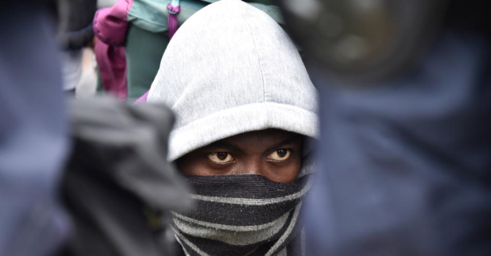 24.out.2016 - Migrante olha para policiais franceses de guarda após tumulto durante a evacuação completa do campo de Calais