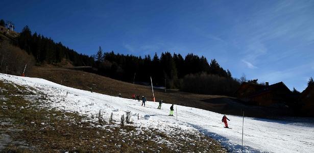 Turistas deslizam pela fina camada de neve em no resort francês de esqui Maribel, nos Alpes, às vésperas do feriado de Natal, na França - Jean-Pierre Clatot/AFP