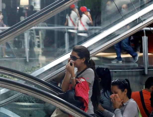 Pessoas se protegem do gás lacrimogêneo dentro de um shopping center após confrontos entre forças de segurança e manifestantes oposicionistas, em Caracas