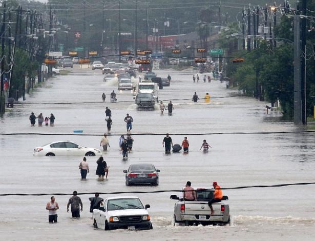 27.ago.2017 - Pessoas caminham por região inundada pela passagem da tempestade tropical Harvey, em Houston, EUA - Thomas B. Shea/ Reuters