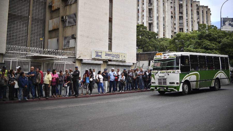 14.mar.2019 - Venezuelanos fazem fila para esperar ônibus depois que o governo decretou o fim do apagão de uma semana e chamou os trabalhadores para voltarem aos seus postos - Yuri Cortez/AFP