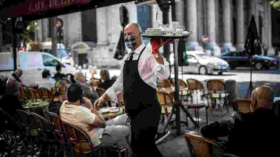 Um garçom trabalha no terraço do Cafe de Flore em Paris; cafés e restaurantes reabriram hoje na França - Martin BUREAU / AFP