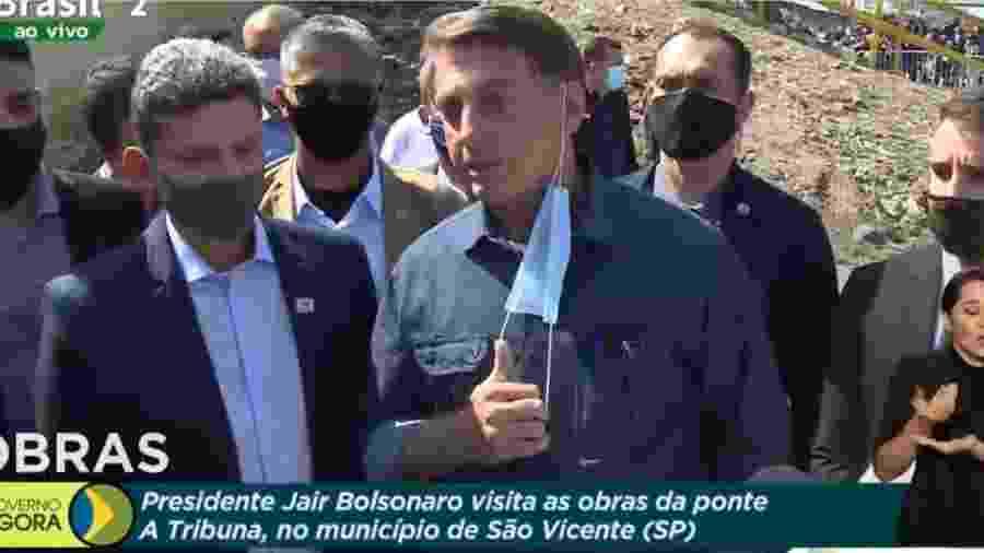 O presidente Jair Bolsonaro (sem partido) tira máscara ao visitar a Ponte dos Barreiros, em São Vicente, no litoral paulista - Reprodução