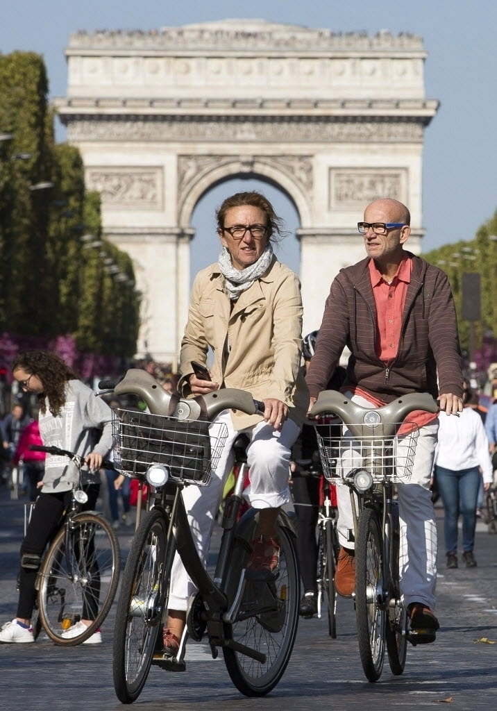 27.set.2015 - Casal passeia de bicicleta pela avenida Champs Elysee durante o