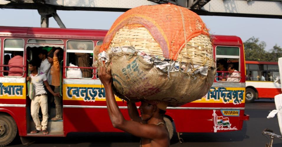 Cruzando a cidade. Um homem carrega uma cesta na cabeça pela ponte Howrah, no centro de Calcutá, na Índia. A ponte em consola tem o maior tráfego de pessoas por dia no mundo do que qualquer outra do tipo