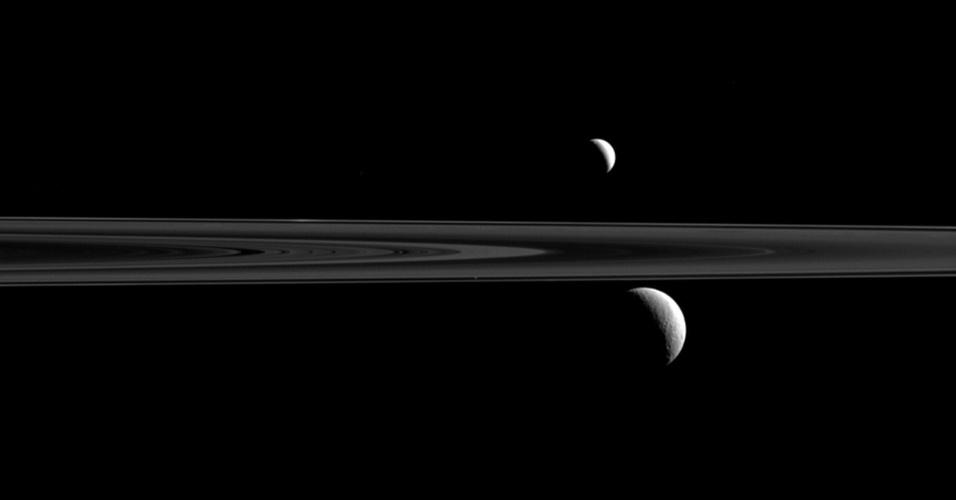 4.jan.2016 - A sonda espacial Cassini-Huygens tirou uma fotografia do que parecia ser um par de satélites de Saturno, mas na verdade era um trio. A imagem mostra claramente Enceladus (acima dos anéis) e Rhea (abaixo). Porém, de acordo com a Nasa (Agência Espacial Norte-Americana), Atlas também está na foto e pode ser encontrado logo acima e a à esquerda de Rhea. A imagem foi tirada de uma distância de aproximadamente 2,8 milhões de quilômetros de Rhea e 2,1 km de distância de Enceladus, e 2,4 milhões de km de Atlas