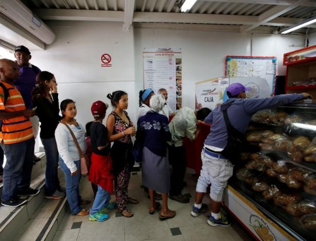 Pessoas fazem fila para comprar pão em padaria estatal em Caracas, na Venezuela