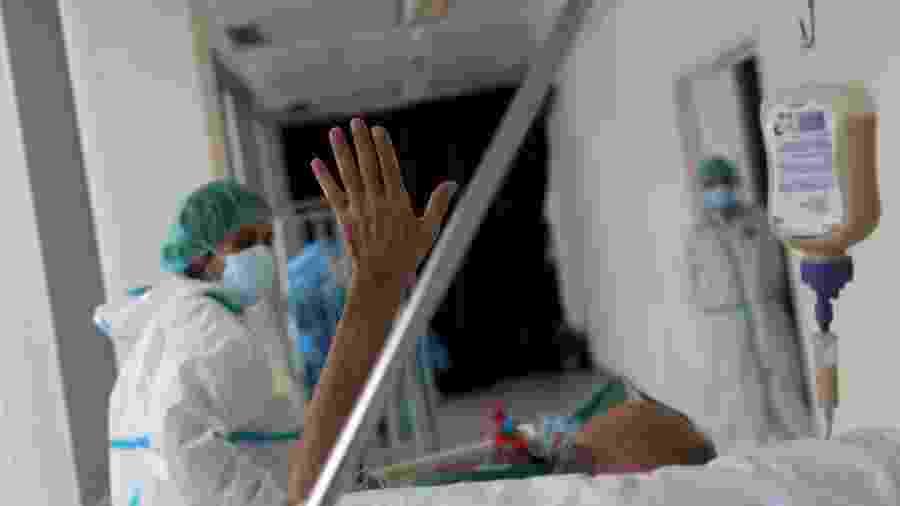 Paciente em recuperação da covid-19 acena quando é levado para um quarto de hospital regular após passar mais de cinquenta dias na unidade de terapia intensiva (UTI) do hospital da Universidade Infanta Sofia em Madri, Espanha - SUSANA VERA/REUTERS