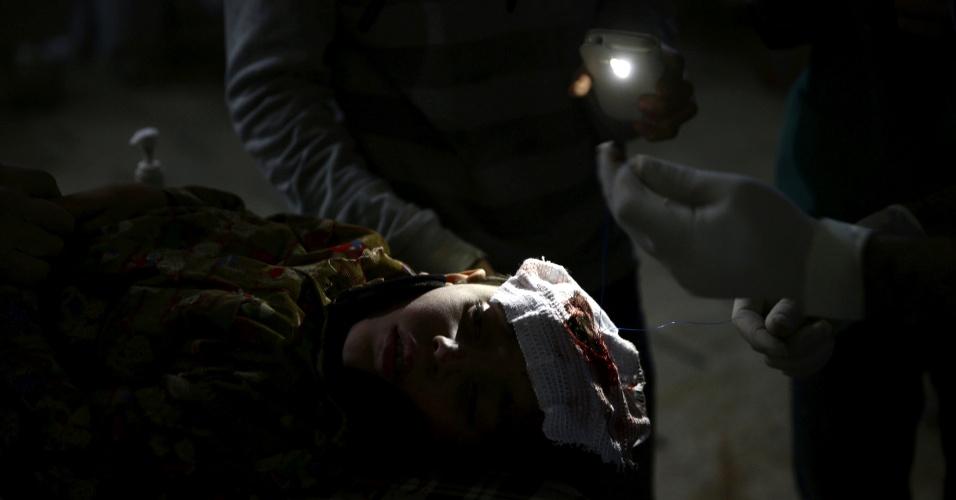Com o auxílio da lanterna de um celular, médico faz a sutura ao atender um jovem no hospital improvisado de Douma, na Síria, cidade controlada por rebeldes. O local é alvo de bombardeios e ataques do Exército do presidente Bashar al-Assad
