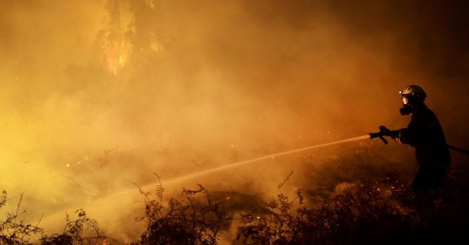 28.dez.2015 - Bombeiro tenta conter incêndio em floresta próxima à cidade basca de Berango, na Espanha