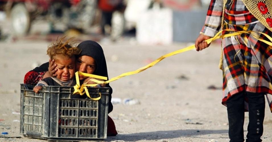 6.fev.2016 - Crianças brincam com caixa de plástico encontrada na rua em Najaf, no Iraque
