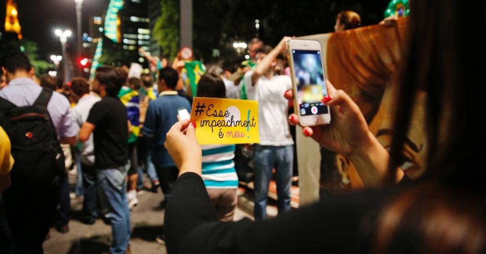 16.mar.2016 - Manifestante tira foto para redes sociais de mensagem que exige impeachment de Dilma Rousseff (PT), na avenida Paulista