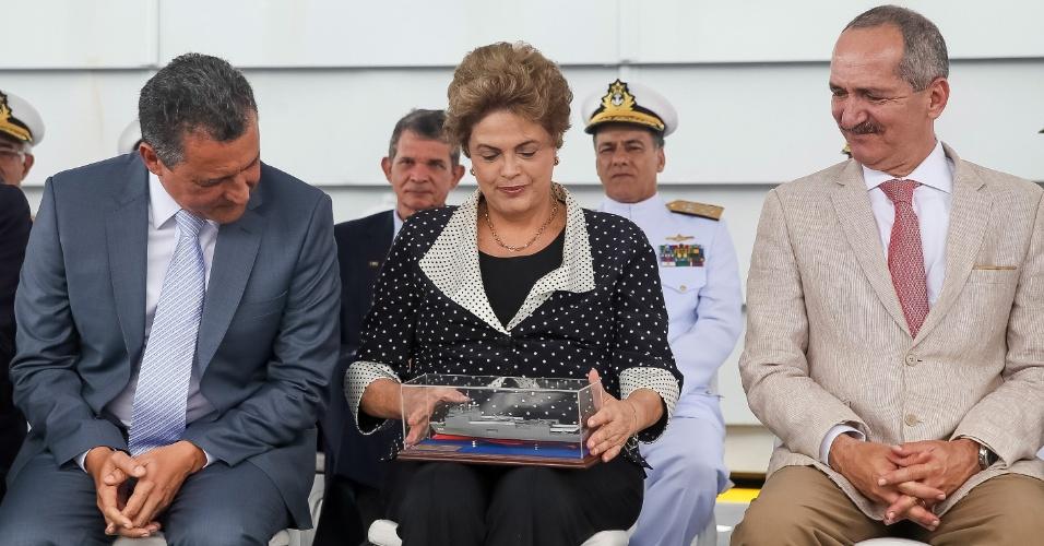 6.abr.2016 - A presidente Dilma Rousseff segura miniatura durante cerimônia de apresentação de novo navio da Marinha, em Salvador (BA)