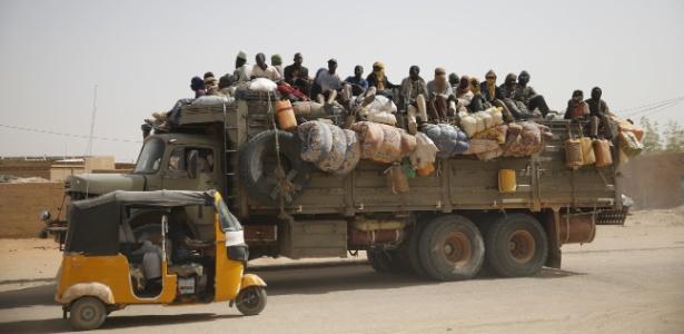 Imigrantes viajam com seus pertences em cima de caminhão em Agadez (Níger)