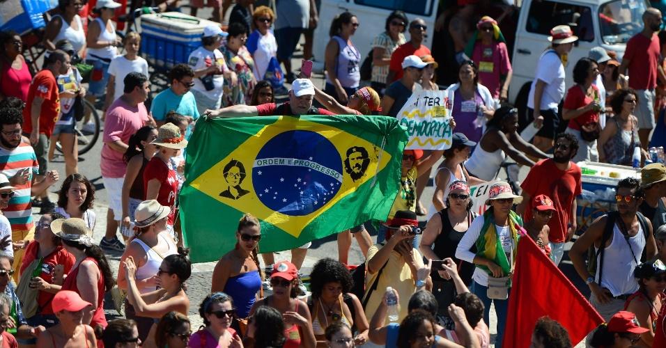 """17.abr.2016 - Manifestante contrário ao impeachment insere imagens da presidente Dilma Rousseff e do guerrilheiro argentino Ernesto """"Che"""" Guevara em uma bandeira do Brasil, durante protesto em Copacabana, no Rio de Janeiro (RJ)"""