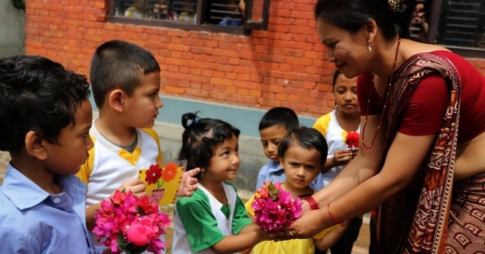 20.jul.2016 - Alunos entregam flores para professora em comemoração ao Dia do Professor em Katmandu, no Nepal