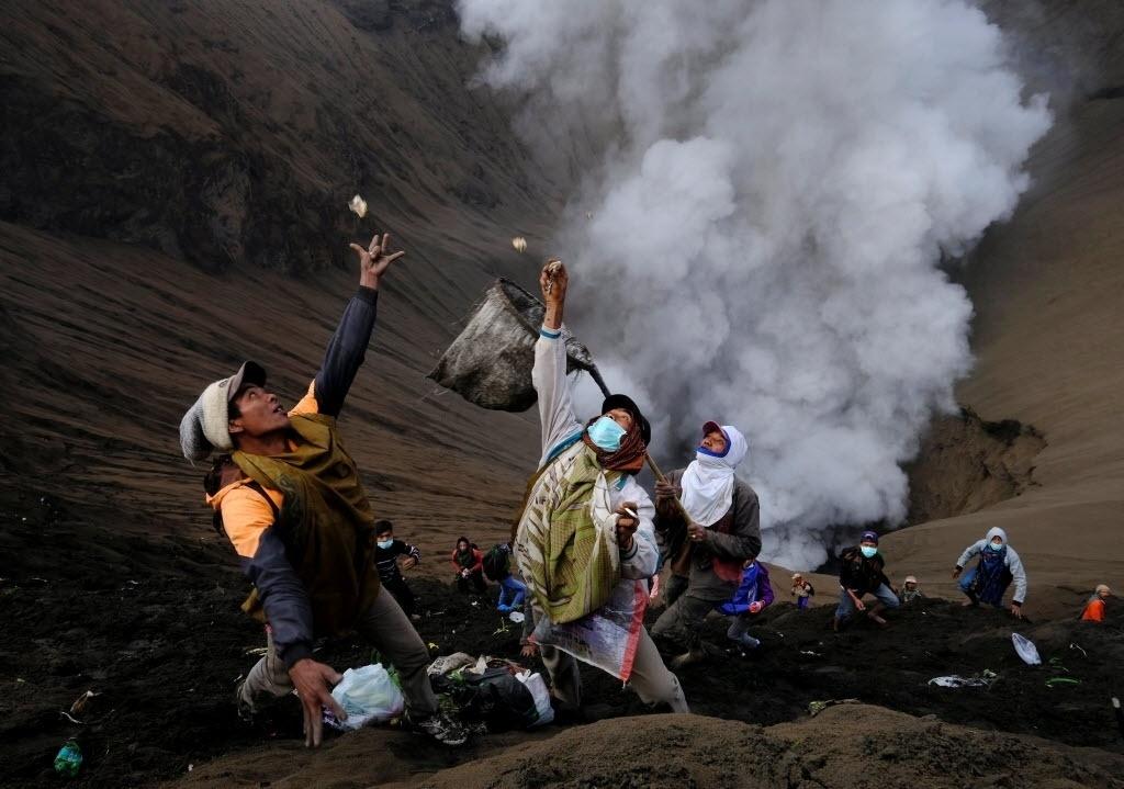 21.jul.2016 - Aldeões participam de ritual na borda da cratera do vulcão Monte Bromo em Probolinggo, na Indonésia. Os moradores organizam a cerimônia de Kasada e lançam na cratera vulcânica oferendas como frutas, arroz, legumes, flores e faz sacrifícios de animais para os deuses da montanha