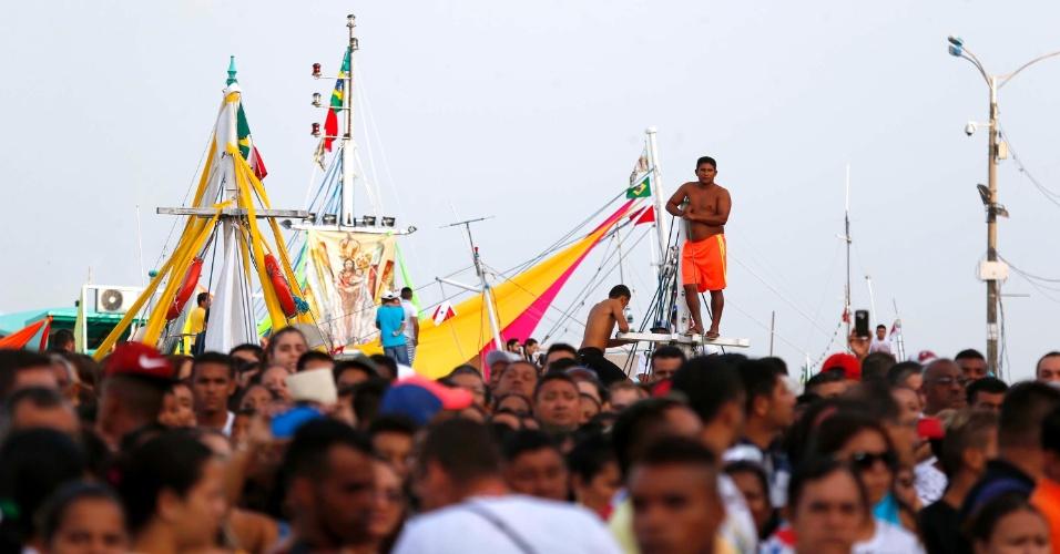 9.out.2016 - Homem se equilibra sobre uma das embarcações participantes do Círio de Nazaré, em Belém (PA), neste domingo, enquanto a multidão acompanha a procissão por ruas da cidade