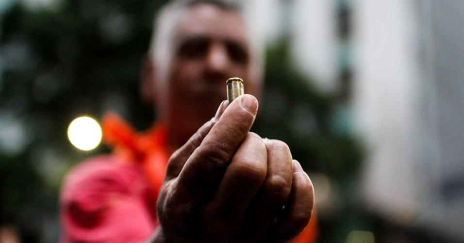 9.fev.2017 - Manifestante segura bala de revólver que teria sido disparada pela PM do Rio durante repressão a protesto na Alerj