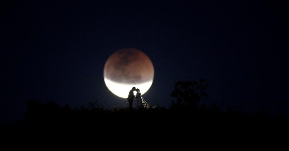 27.jul.18 - Casal de noivos posa para fotos diante da lua de sangue em Brasília (DF)