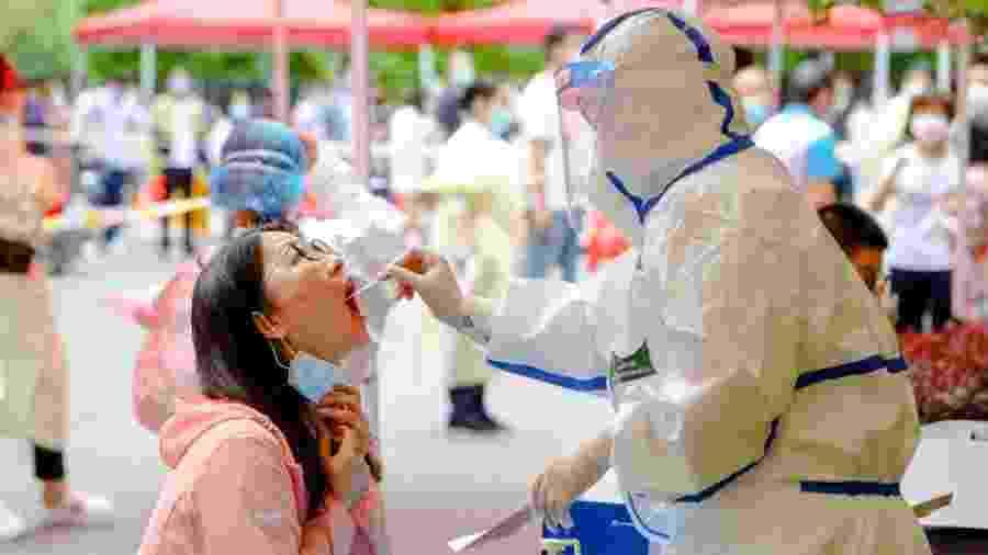 Mulher passa por teste para o coronavírus em Wuhan, região em que se iniciou a pandemia da covid-19 - China News Service via Getty Images
