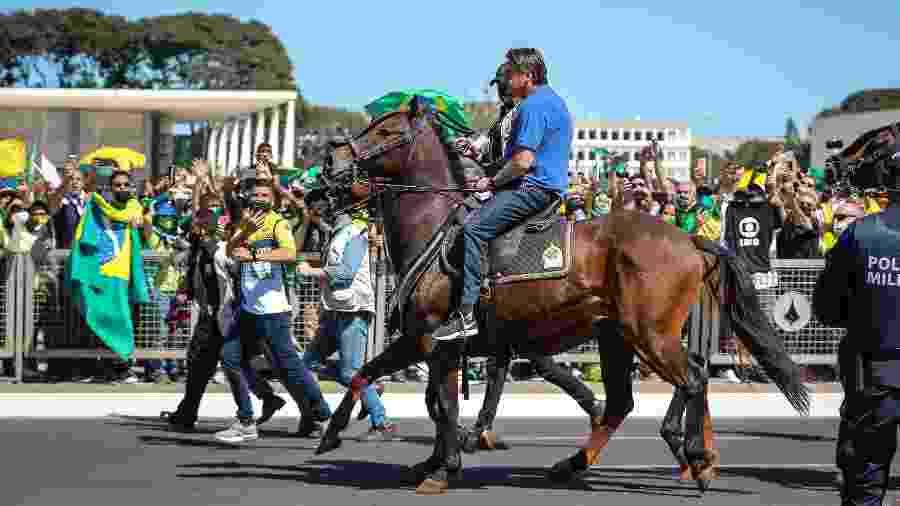 31.mai.2020 - Andando a cavalo, presidente Jair Bolsonaro (sem partido) passa por manifestação de apoiadores em frente ao Palácio do Planalto - Wagner Pires/Futura Press/Estadão Conteúdo