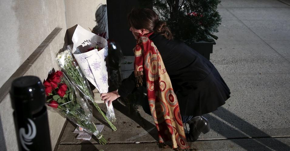 13.nov.2015 - Mulher deposita flores em memorial improvisado no lado de fora do consulado-geral da França em Nova York, logo após os atentados em Paris que deixaram pelo menos 120 pessoas mortas