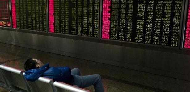 Investidor dorme diante dos painéis que mostram os movimentos da Bolsa de Pequim