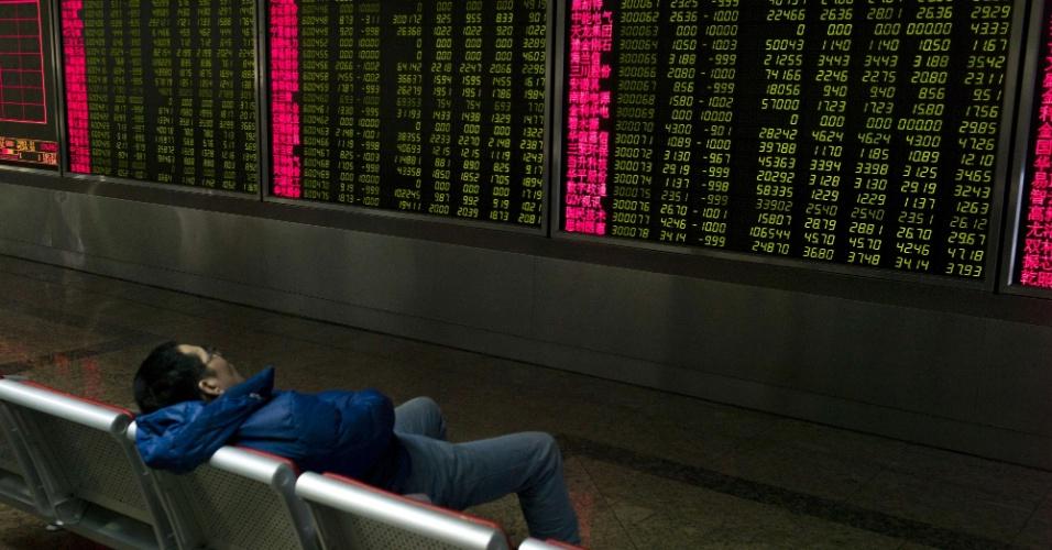 7.jan.2015 - Investidor dorme diante de telas mostrando os movimentos da bolsa de valores de Pequim. Pela segunda vez nesta semana, as negociações foram suspensas no mercado chinês, depois do valor das ações caírem mais de 7% - hoje isto ocorreu em menos de 30 minutos de pregão. A desconfiança dos investidores foi motivada pela decisão do banco central chinês de desvalorizar em 0,51% a taxa de câmbio do yuan