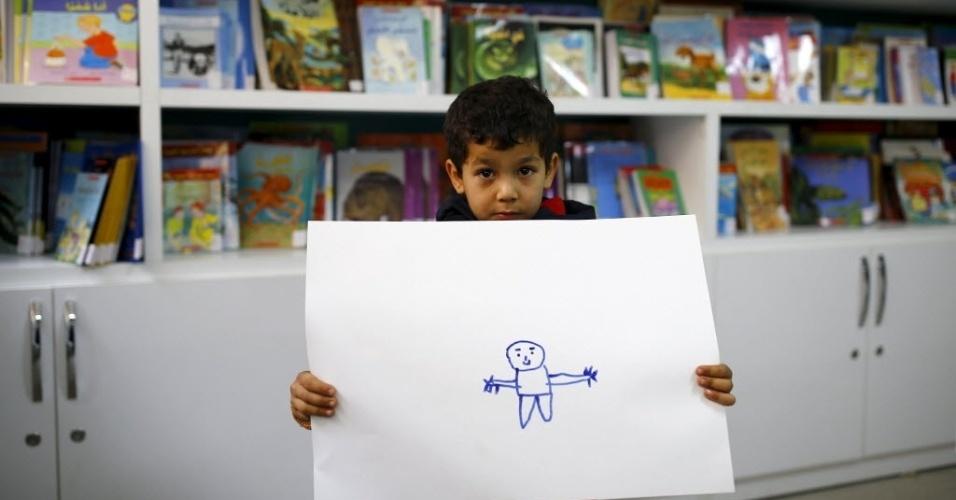 """o Menino sírio Gays Cardak, 6, mostra o seu desenho em uma biblioteca escolar no campo de refugiados na província de Hatay Yayladagi, perto da fronteira turco-síria, na Turquia. """"Eu vou ser um médico e um engenheiro. Nós, os engenheiros vamos reconstruir a Síria, e eu vou levar os [soldados] para o hospital"""", disse Cardak. A guerra civil na Síria, que já deixou centenas de milhares de mortos, empurra outros tantos para o exílio, entre muitos deles crianças. Os desenhos das crianças do acampamento mostram memórias de suas casas, traumas vividos e esperanças para o seu futuro. Dos 2,3 milhões de refugiados sírios que vivem na Turquia, mais da metade são crianças"""