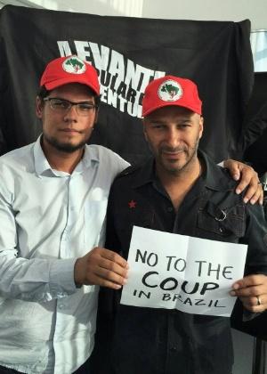 """Tom Morello, com boné do MST, segura cartaz que chama impeachment de """"golpe"""""""