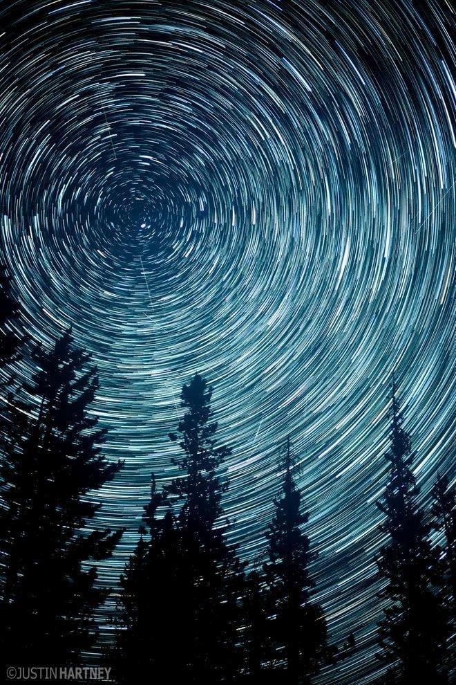 """13.jul.2016 - Os """"riscos"""" no céu são estrelas. Esse efeito se consegue quando se fotografa durante minutos e até horas uma imagem com apenas um """"click"""". O fotógrafo Justin Hartney ama registrar imagens em longa exposição --como é chamada essa técnica. Para fazer a imagem ele posicionou sua câmera na direção à Estrela do Norte. A foto foi feita em Bend, Oregon (EUA)"""