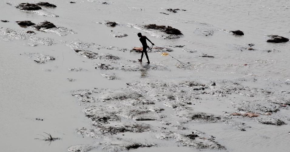 2.set.2016 - Homem puxa um ímã para encontrar moedas jogadas pelos devotos como oferendas religiosas no rio Ganges em Allahabad, na Índia