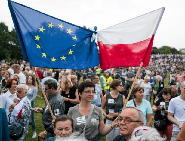 23.jul.2017 - Mulher segura as bandeiras da União Europeia (esq) e da Polônia durante protesto contra legislação da Suprema Corte, em Poznan, na Polônia