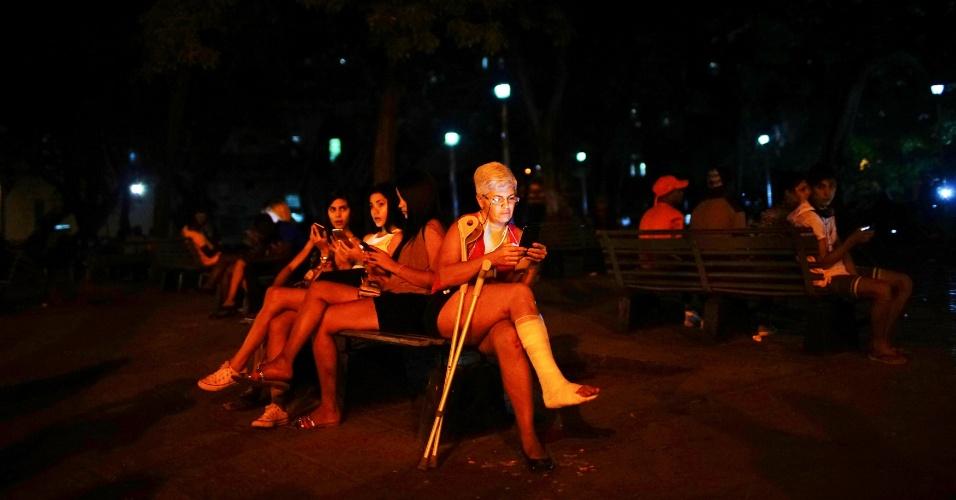 Uma idosa e três jovens usam seus celulares para acessar a internet, em Havana