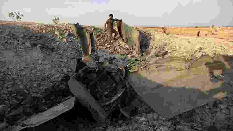 Combatente rebelde caminha pelos destroços de um avião do regime sírio abatido por jihadistas em Khan Sheikhun, na província de Idlib, em agosto - Omar Hj Kadour/AFP